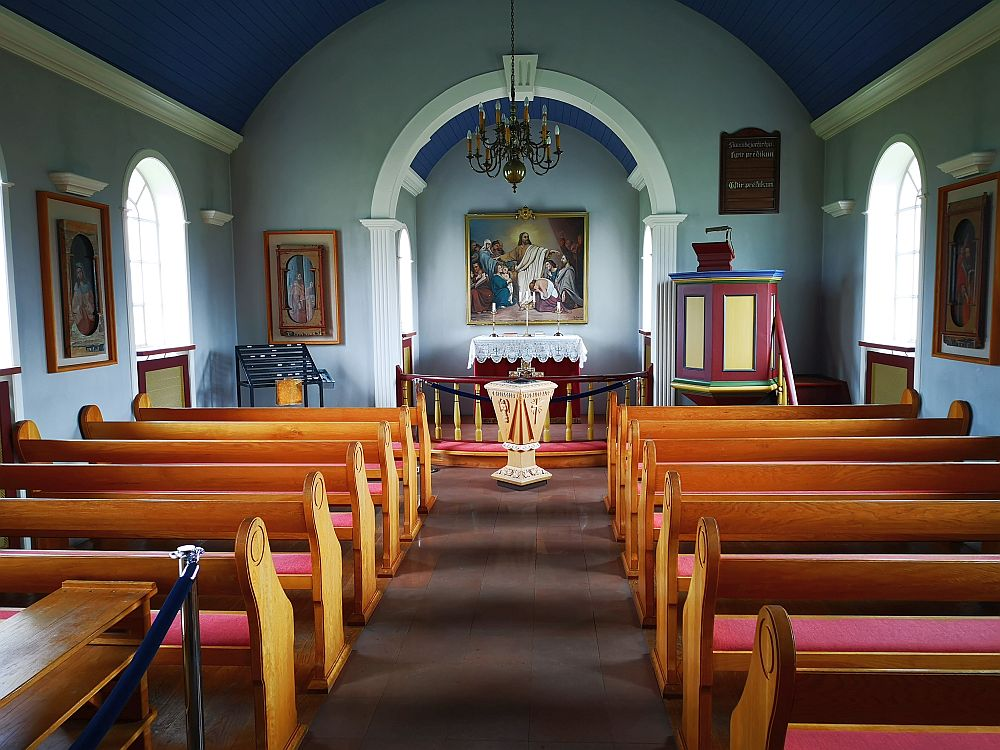 Looking straight down the aisle toward the altar. Pews on either side: wood with red seats. At the end of the room is an archway with a railing dividing it from the main room. A religious painting on the far wall, over a lace-covered altar. The pulpit is before the archway to the right, and painted simply: dark red and yellow. The ceiling is arched and dark sky blue. The walls are light blue with white trim.