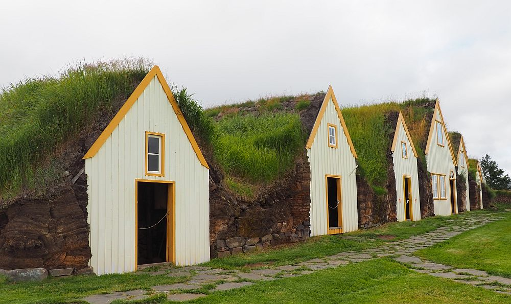 The gables look like how a child might draw a house: door in the center, one window above the door. Each is painted off-white with yellow trim along the roof line and around windows and doors. Between the gables is turf covered with grass.