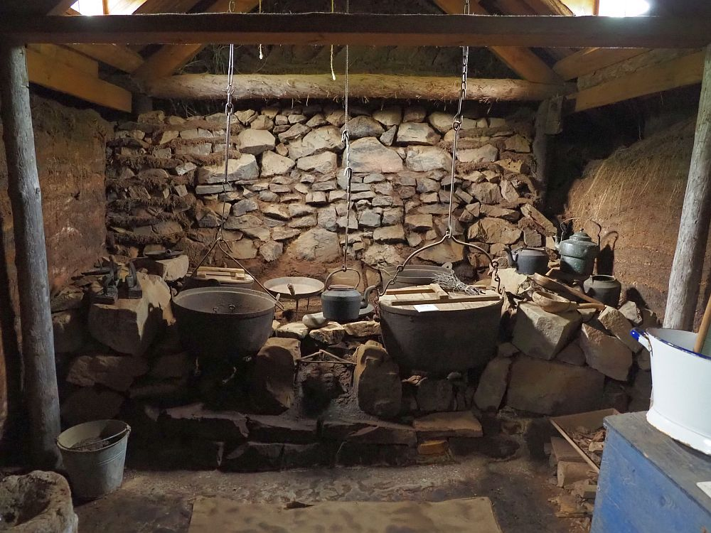 A wall of rocks lines the back wall of the room. In front of that is a shelf of rocks. Several pots sit on the rocks or hang from chains from the ceiling. A kettle and some smaller pots stand on the rocks to the right. The walls on the left and right are bare turf and the floor is dirt. The light comes from two skylights, one on each side in the roof above the hearth.