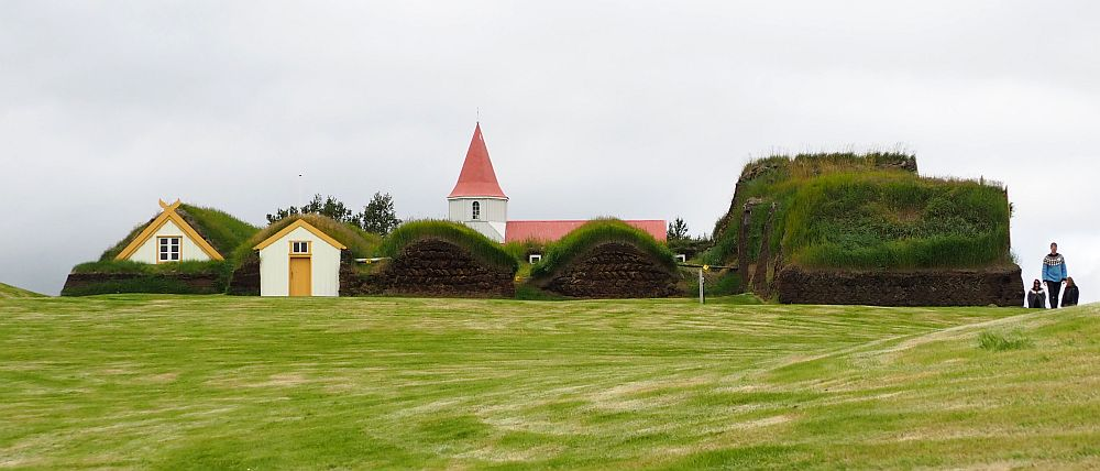 From the side only 2 gables are visible to the left. Most of the structure looks like a bunch of grassy lumps. The steeple of the church can be seen behind the house: it is pointy and red.