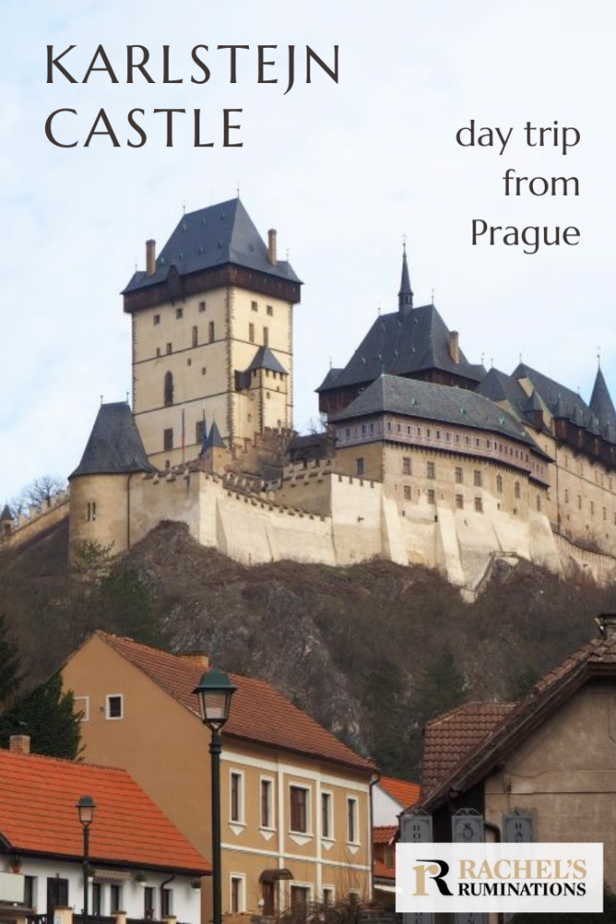 Pinnable image Text: Karlstejn Castle, day trip from Prague Image: view up to the castle, with the village at the bottom and the castle looming above it.