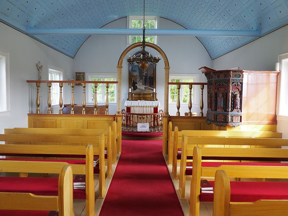 Looking down the aisle of the church. Pews on either side, wood with red seats. A railing dividing the pews from the altar. The altar has a large painting above it. On the right, before the railing, is the old pulpit, carved with saints. The walls are clean white and the ceiling is arched and painted light blue.