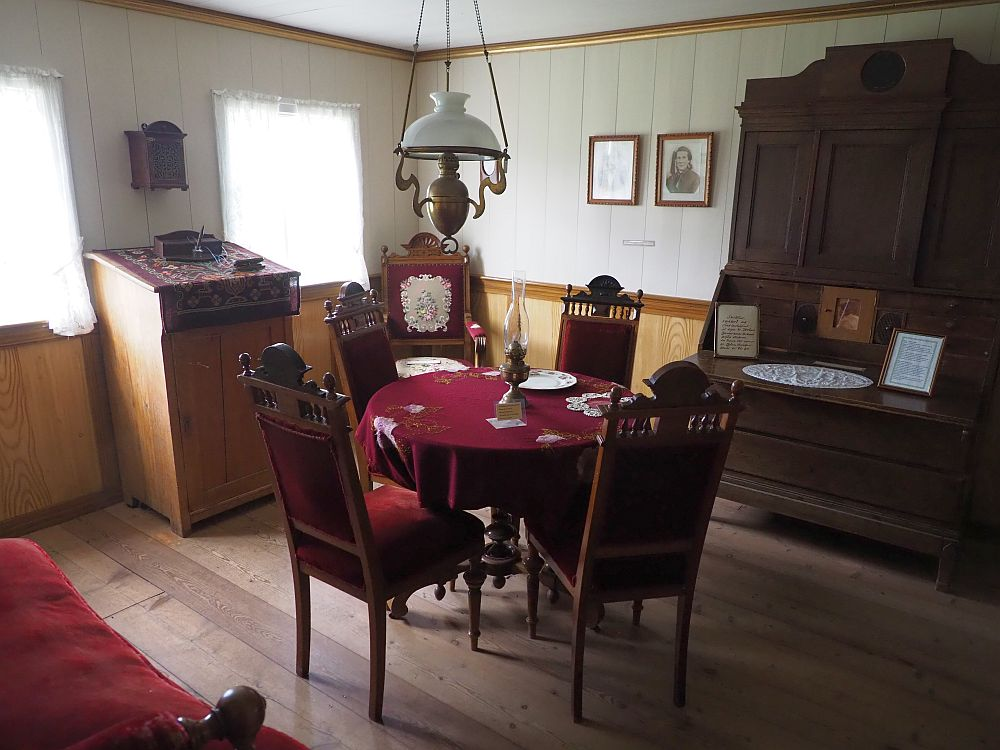 The floor is wood boards, and the bottom half of the walls are panelled. Above the paneling the walls also appear to be wood boards, but painted off-white. On the left back wall are two windows, light coming through white curtains. Between the curtains is a writing table with a slanted top. In the far corner is an upholstered red chair. On the right back wall two portraits hang and then next to them is a large cupboard, perhaps a secretary. In the middle of the room is a round table covered in heavy red cloth with an oil lamp in the center. Around it are four upright chairs upholstered in red. On the near left wall (the photo was taking from a door in the corner) a bit of a red upholstered sofa is visible.