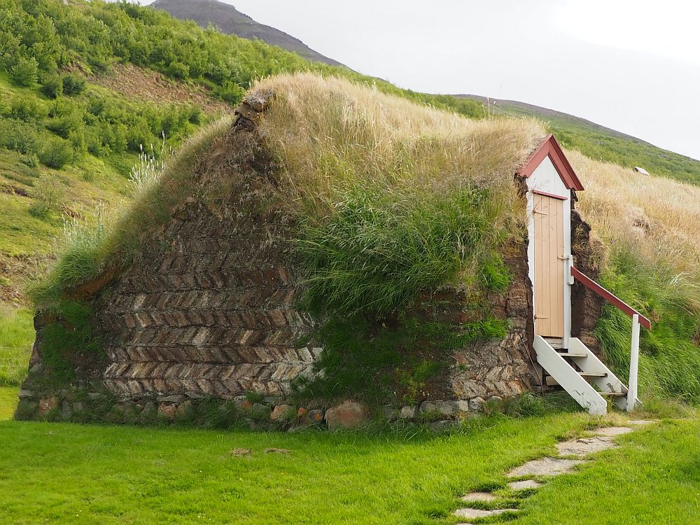 "The ""house"" looks almost like a grass-covered hill except that the side facing the camera has visible brown turf bricks in a herringbone pattern. On the side is a door leading into a grassy turf wall. A few short steps lead up to the door."