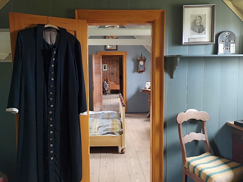 This photo looks through a doorway, through a room, and into a third room. In the nearest room, the walls are wood and painted a grayish blue. A pastor's robe hangs on the back of the open door on the left. On the right is a chair at a desk. The light comes from a window (out of frame) above the chair. On the wall above the chair and next to the door is a fraimed portrait. IN the next room the end of a double bed is visible. On the wall next to the next door is a clock. Through that door the end of a single bed is visible.