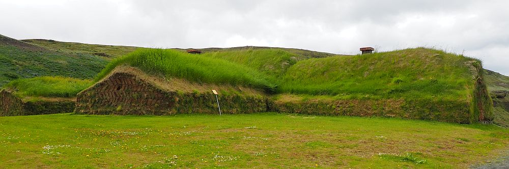 The turf house has bright green grass on the roofs. Two wings are visible in this photo, both extending out from the center of the photo. The left wing's end is visible: brown turf bricks.