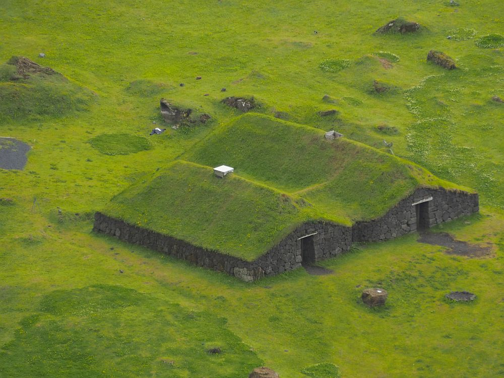Seen from an angle above, the roofs are green and the field around the building is also green. It has two long rooms, each with a peaked roof. The holes in the center of each roof are capped with something that may be modern metal or plastic. The walls are quite low and built of stone. They The end of both halves of the building has a door, and the building is high enough in the middle for a person to stand upright. At the sides, though, these walls are very low, about half as high as the center under the peaks.