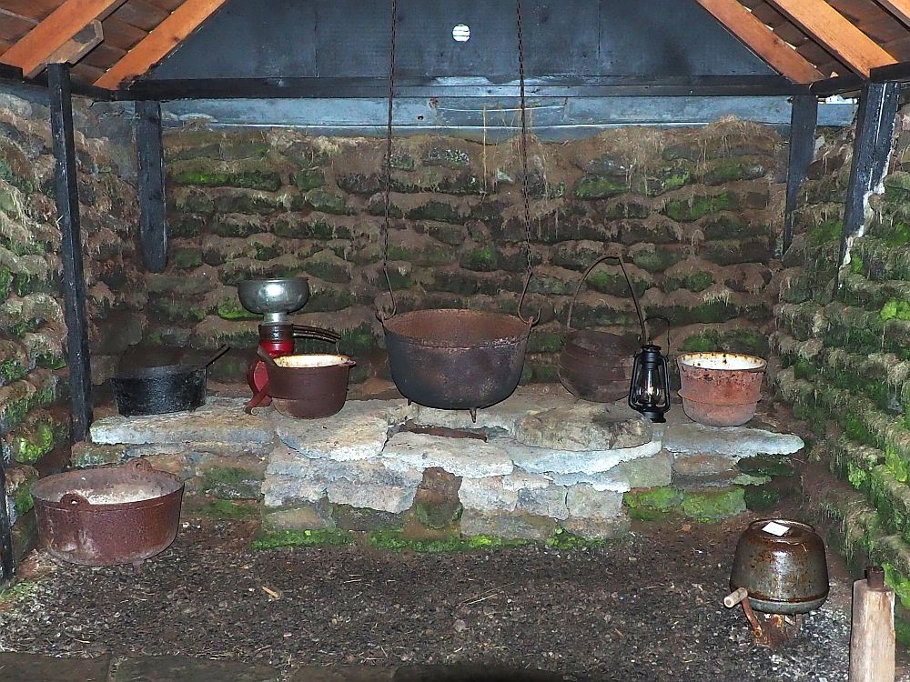 "The ""stove"" is a pile of flat stones built into the end of the room. On top are several iron pots, and one large pot hangs on chains from the ceiling. The walls behind the stove and on either side are turf, with green moss growing on it in some places. Beams of wood stand vertically against the walls and hold up the beams that support the ceiling."