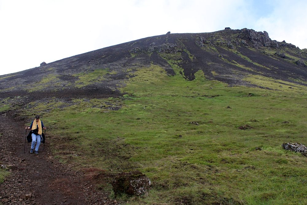 A hill, covered in low grass or moss but with exposed rock on the top. On the left of the picture I am walking down a gravel path, holding two sticks and looking down at the ground. On my way to Reykjadalur hot spring thermal river.
