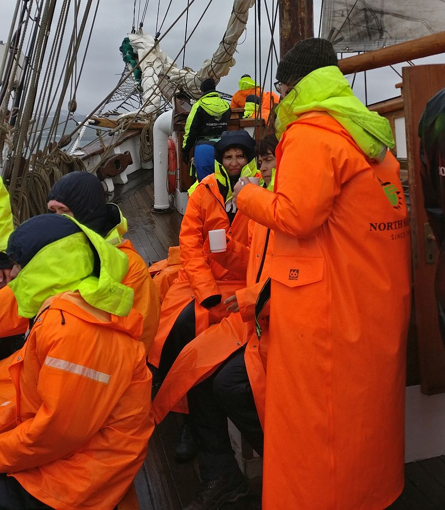 A group of people sit in two rows, each wearing bright orange raincoats. The yellow collars of their coveralls show, sticking out from the necks of their raincoats. Behind them the bow (front) of the ship is visible, rigging with a furled sail.