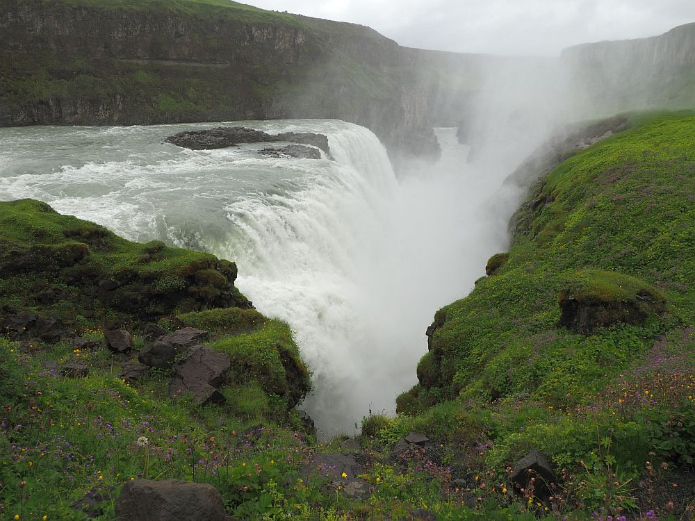 The water plunges off a flat shelf with white rapids plunging into a deep cut between green hilly land. Dimly through the mist thrown up over the cleft, the river flows away in the distance between cliffs.