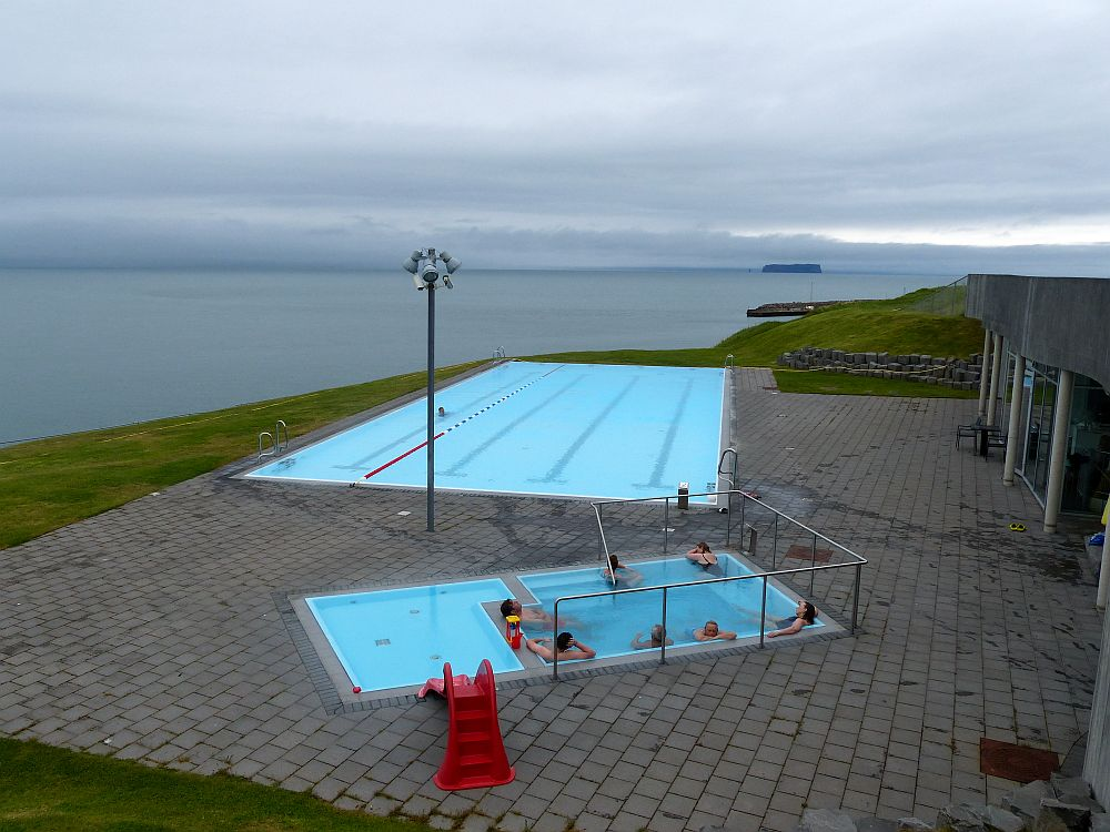 A view from slightly above of the pools at Hofsos: in the foreground, the hot bath and the children's pool right next to it, with a small slide into it. Beyond, the rectangular swimming pool, the lanes visible through the water. Beyond the pools is the water of the bay, with cloud-shrouded land on the other side.