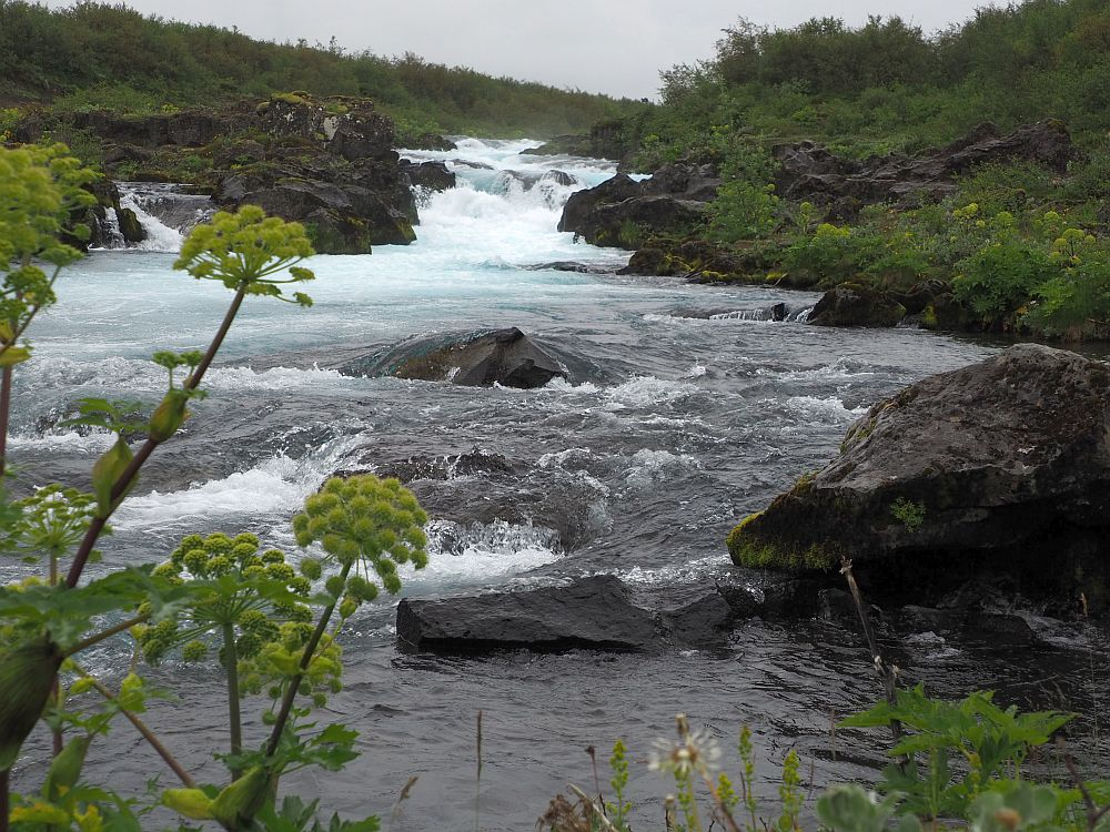 Looking straight upstream, the water flows toward the camera, bumping over various rocks along the way. Rocks on both sides are black, edging the stream, and green bushes are visible on both sides. In places, the water is blue but mostly it is dark grey, except where the rapids look white.