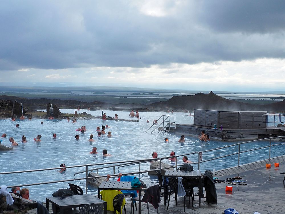 A view of Myvatn Baths. A railing along the near edge of the pool. The water is milky blue and is dotted with people. Another pool beyond, steam rising here and there. A long view into the distance under dark clouds: looks like lakes and islands.
