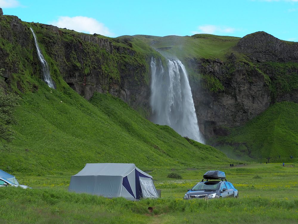 In the foreground, a large camping tent and a car parked next to it with a box on its roof. Behind it, a long cliff, green toward the base, rocky above. Seljalandsfoss is in the center of the photo behind: a wide sheet of water falling from the cliff. At the left edge of the picture, another much smaller waterfall can be seen, just a narrow stream of water from the edge of the cliff.