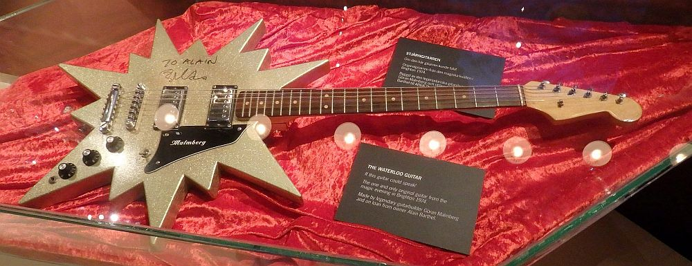 An electric guitar lying on top of a piece of red velvet cloth. The guitar body is shaped like a gold-colored star with 13 points, some long and some short.
