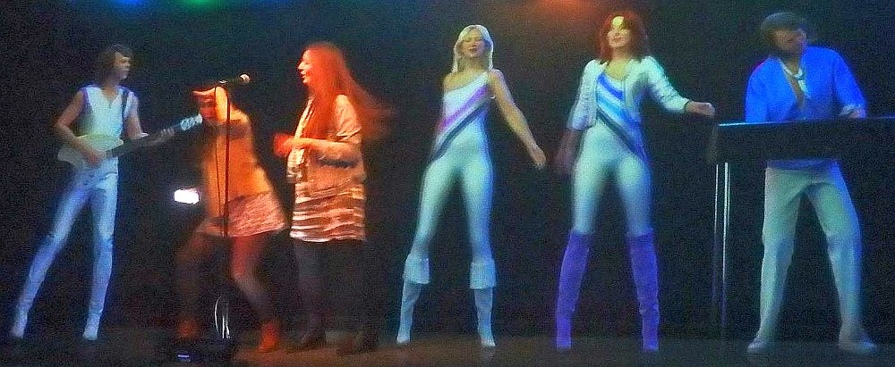 The members of Abba stand in their white spandex outfits against a black background. They are busy performing. Between the left-most ABBA member (Bennie) and Frida are two people, looking orangy under the lights. They appear to be about the same size as the band members.