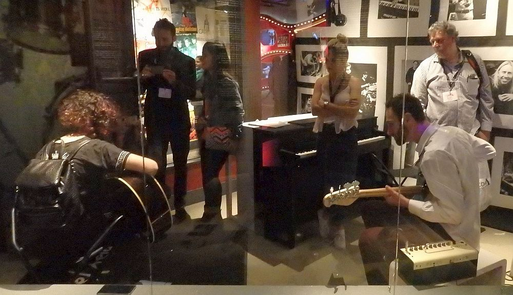Seen through a glass wall, two guitarists sit, back to the camera, each holding and playing a guitar. Beyond them are four other people. Two, on the right, are just standing and watching the guitarists. So are the two on the left, but one is taking a picture as well. A piano stands behind them, and the far wall is covered with photos. In the ABBA Museum Stockholm.