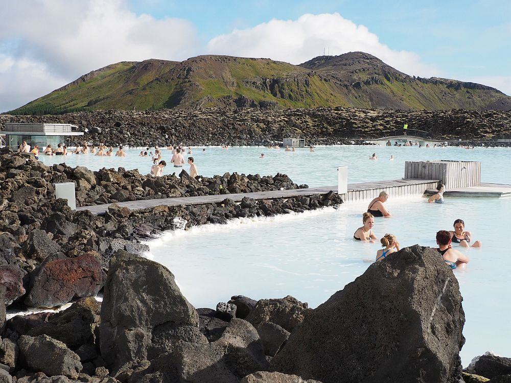 A view of the blue lagoon: milky blue water, edged with piled-up black rocks. People in the water here and there. At the back of the photo is a low hill surrounded by more black rock, covered in spots with green moss.
