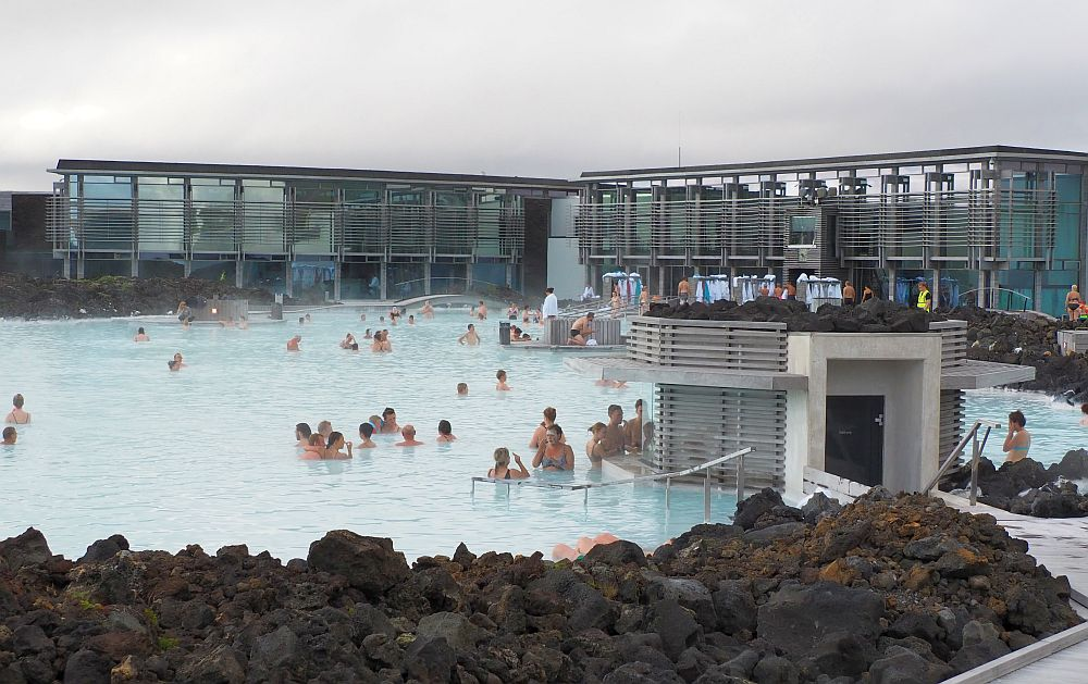Blue Lagoon pool looking toward the building. It is in an L shape, with a glass exterior. People dot the water, with more of them near a small building to the right, where the masks are given out. Piles of black rock in the foreground.