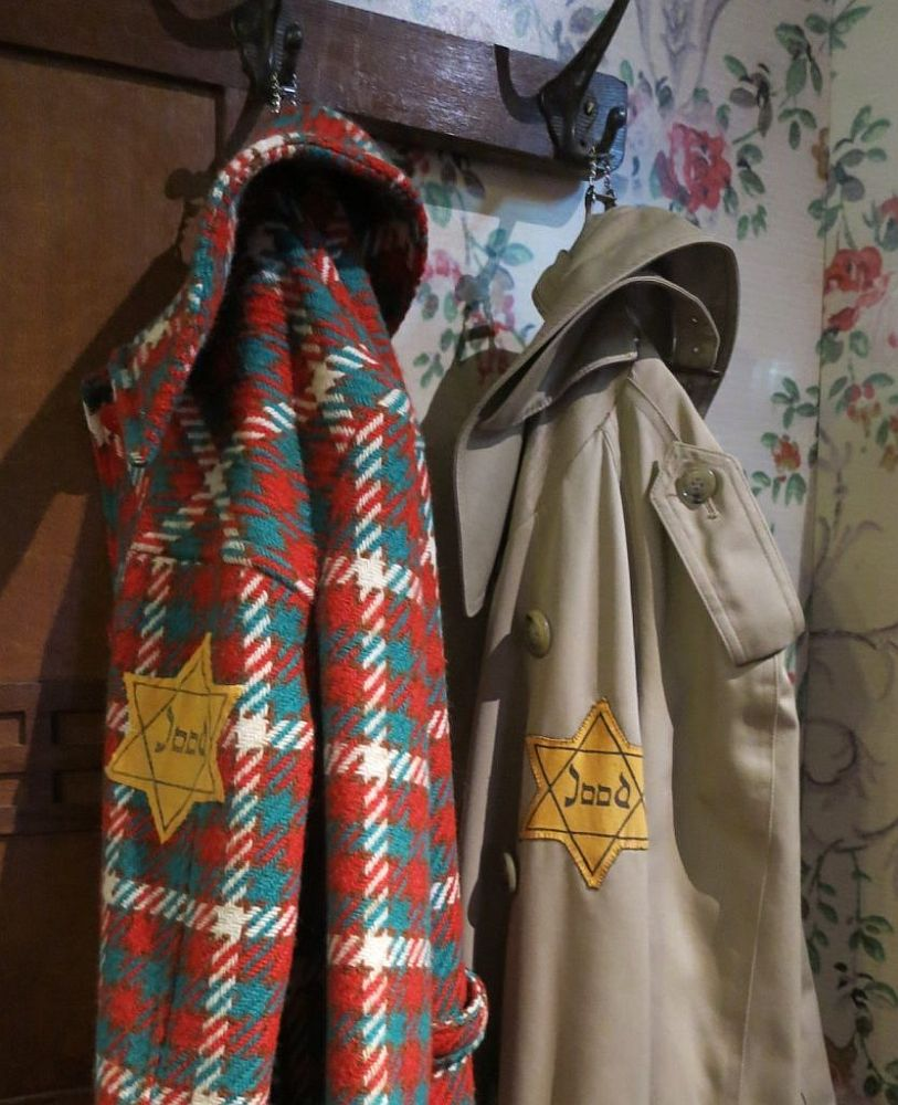 "Two coats hang on a coatrack. The left-hand one is brightly checked in red, green and white. The right-hand one is a trenchcoat in beige. Both have a yellow star of David on the sleeve with the word ""Jood"" inside it, which means ""Jew."""