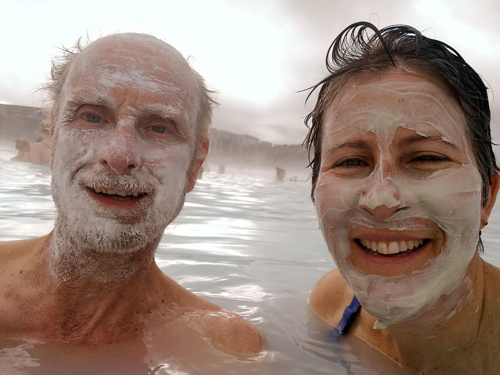 A selfie: my husband on the left, smiling, bald head except some hair on the sides, beard and mustache, face smeared with white mud. On the right, me with my wet hair slicked back, white mud smeared on my face, also smiling. We are up to our shoulders in milky-looking water.