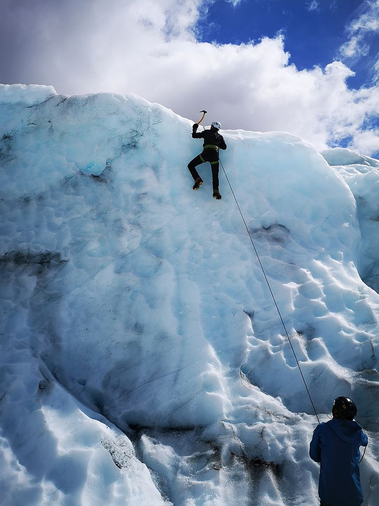 A wall of ice fills the picture except for a bit of sky at the top. At the bottom is a man looking up. He holds a rope. Albert is near the top of the wall. The rope attaches to the thing around his waist and legs. His toes grip the ice and he is mid-swing of the pickaxe into the ice above his head.