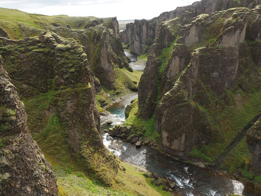 Looking down the length of the canyon: sheer rocky cliffs on either side frame a river that snakes between them.