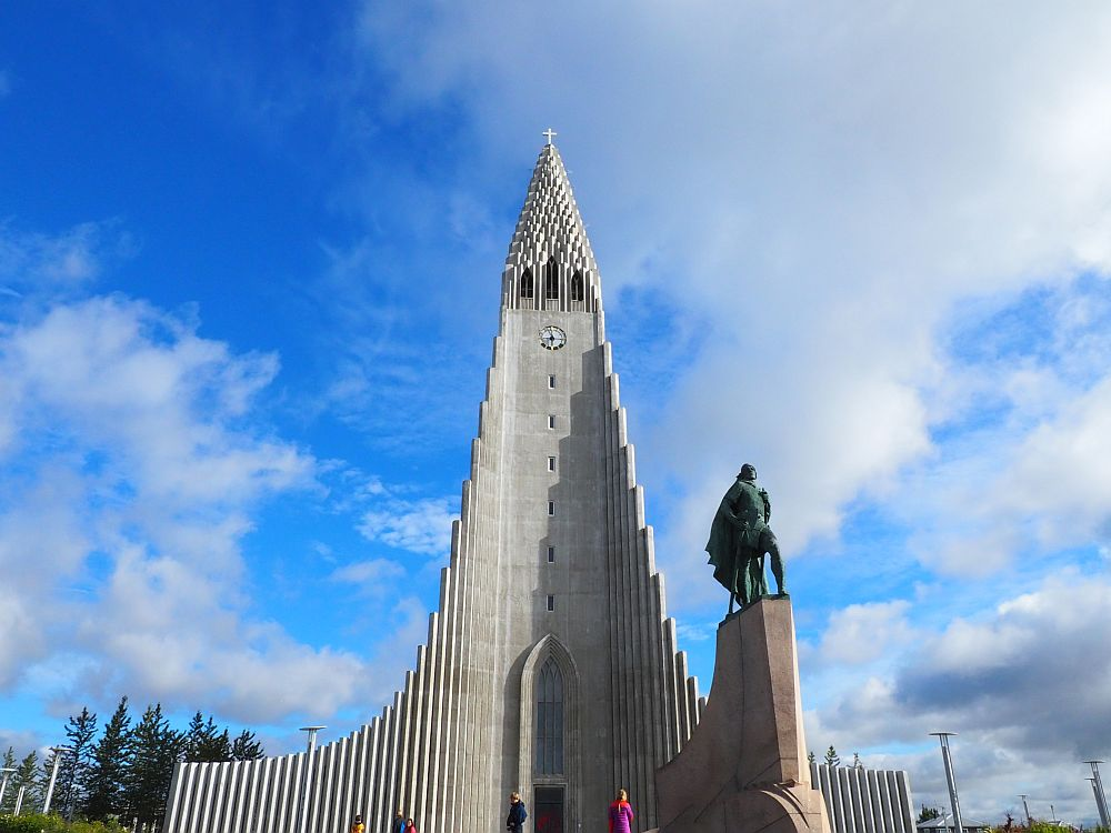 Hallgrimskirkja is made of concrete, with a triangular steeple made of vertical elements of increasing height. In front of it is a statue of Leif Ericson.