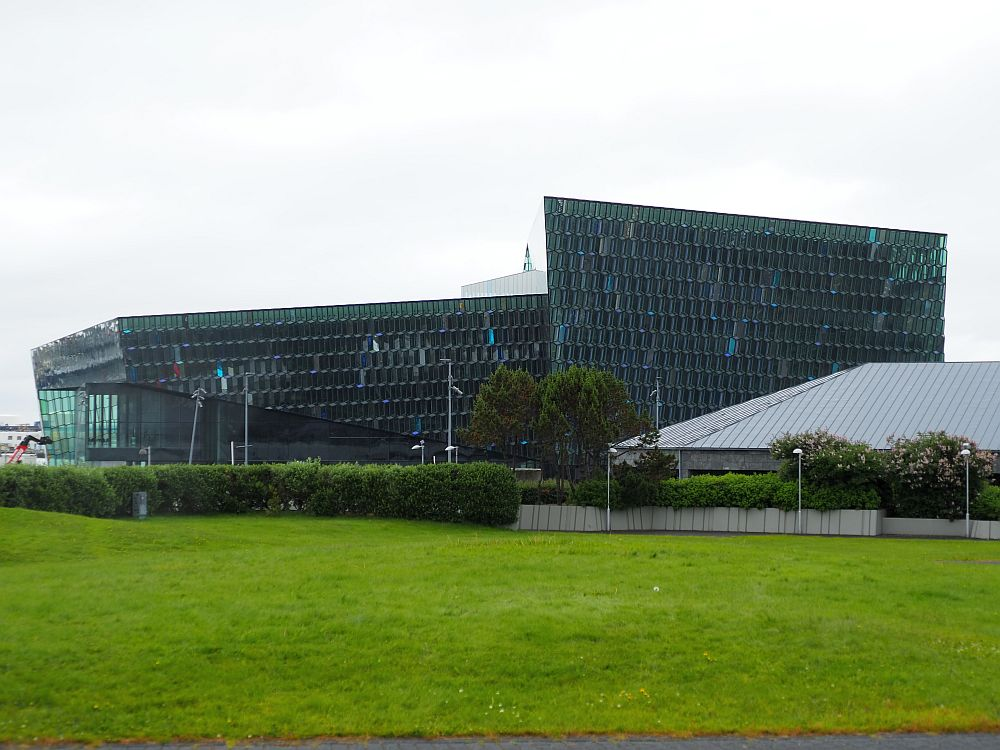 The building is all angles, completely covered in glass panes, looking opaque from this angle on gray day.