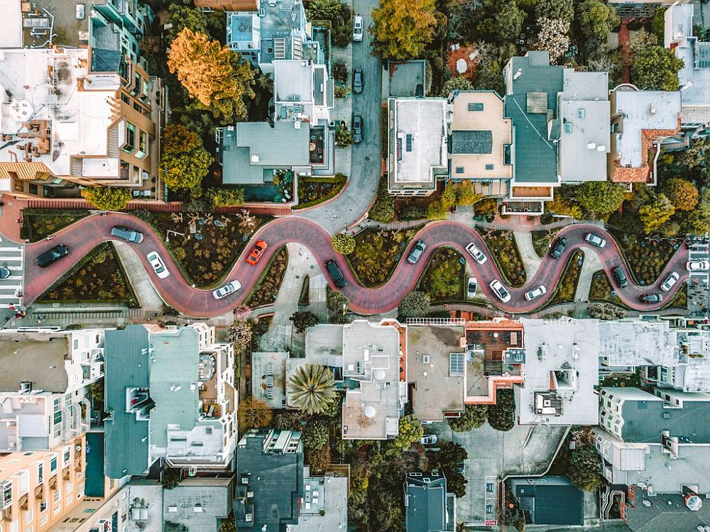 A drone view straight down of Lombard Street. The eight curves of the street are visible, with cars on the street. On either sides, the mostly flat roofs of the buildings on either side, with lots of greenery along the road and between and behind the buildings.
