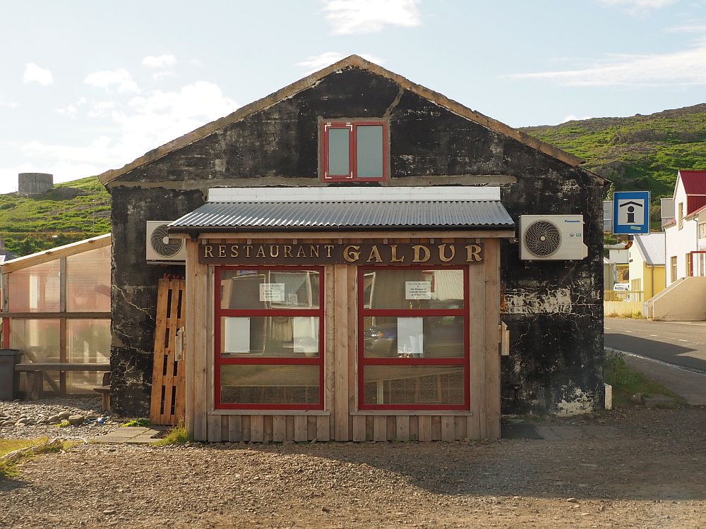 "A brown, not recently painted, low building of one story. Across the front are some big windows and the words ""Restaurant Galdur""."