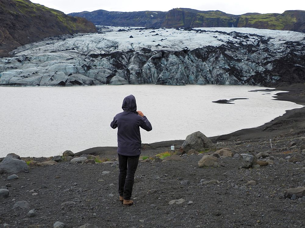 In the foreground, Albert stands with his back to the camera looking toward the glacier, holding his phone to take a picture. In front of him is the meltwater lake, and beyond that is the glacier: a feild of bluish ice with an almost vertical shelf at the lakeside where chunks have broken off.