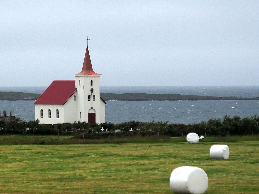 A simple small church: white walls, red roof, simple pointy steeple, faces away from the sea behind it. In front is a field with bales of hay scattered on it, all wrapped in white plastic.