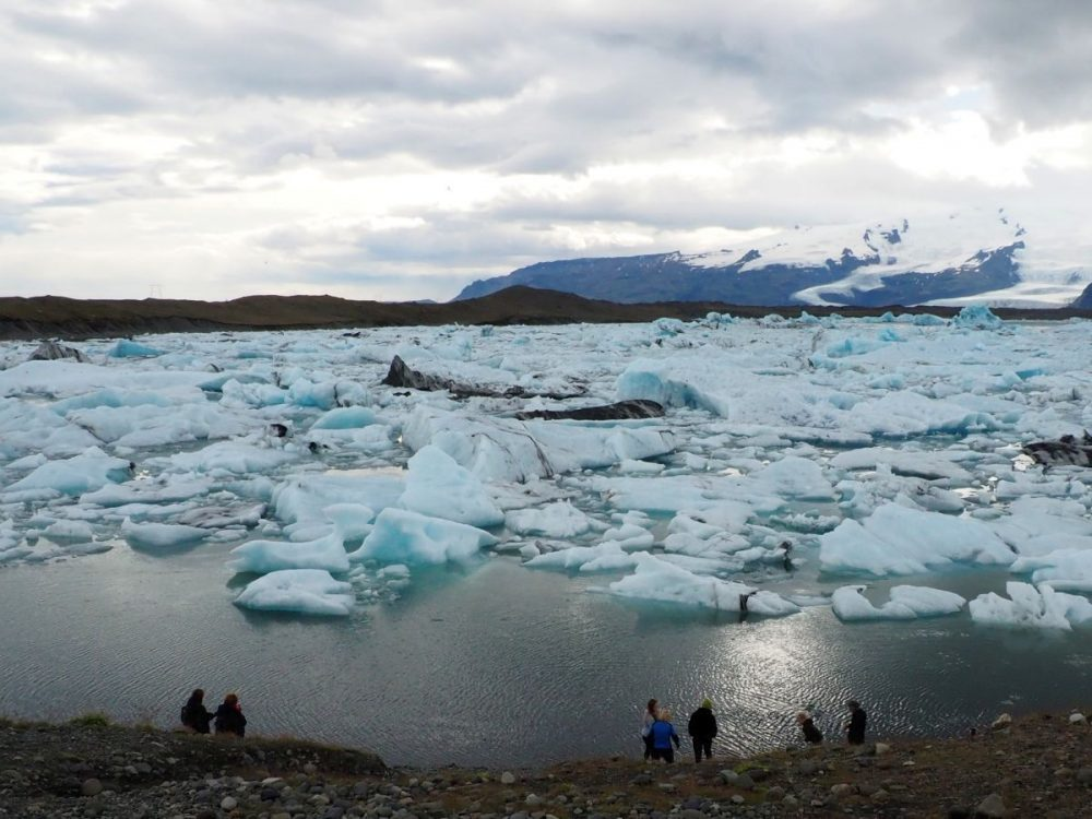 The lagoon is filled with chunks of ice, all looking bluish. Some open water is visible in the foreground, with a few people in sillhouette at the bottom of the picture. Behond the lagoon is a mountain covered in snow.