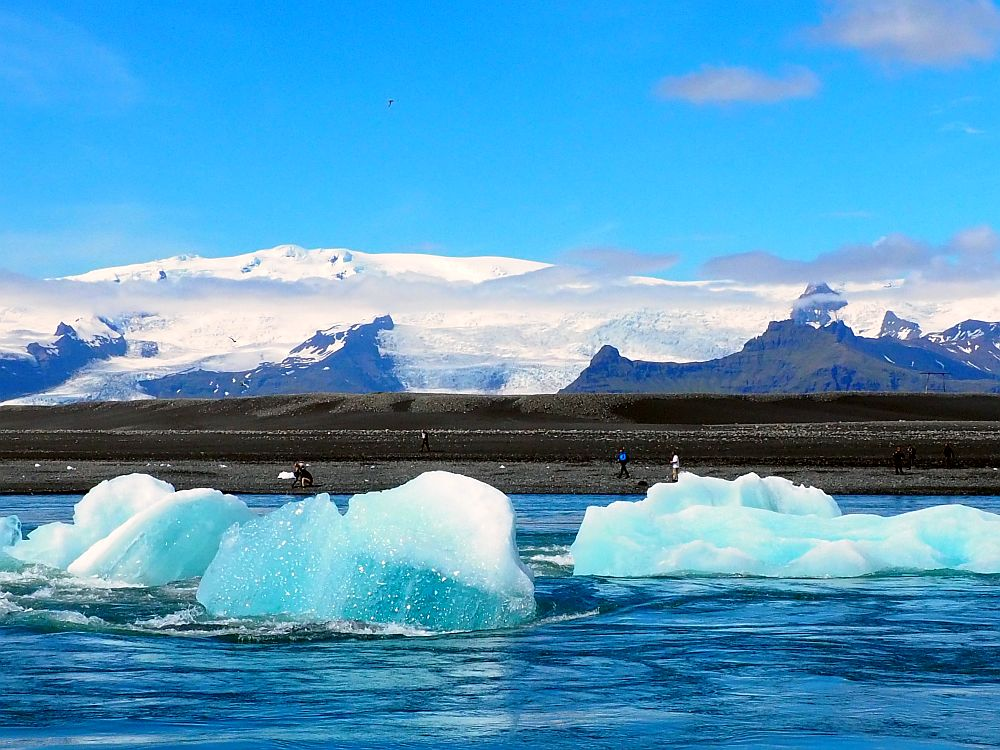In the foreground, a river of blue water with chunks of blueish white ice on it. The far shore is dark grey stone with a few people looking tiny along its edge. Beyond that, a range of mountains topped in white. Two tongues of glacier are visible flowing down from the mountains.