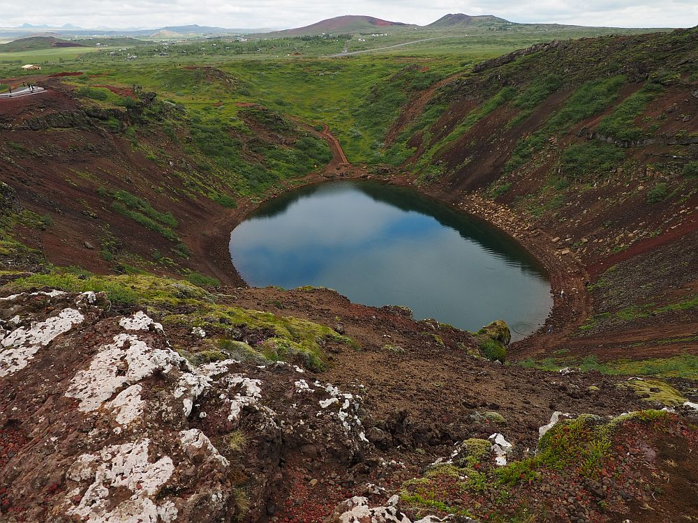 Looking down into the crater, the sides are brown with some low green cover, probably moss. The water is quite dark, reflecting the sky of white clouds and a bit of blue.