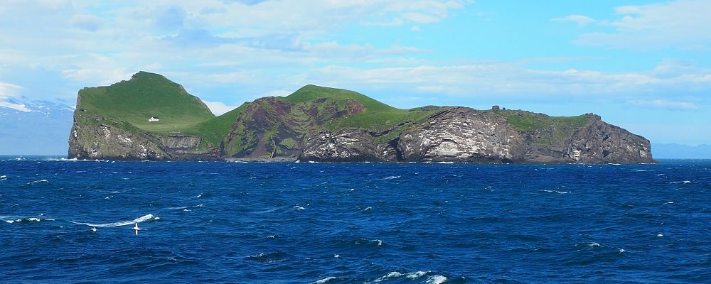 In the foreground, very blue sea. On the horizon, an island, edged by steep cliffs, green on their top. A single house is visible at one end.
