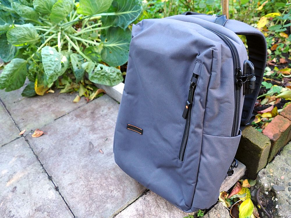 The backpack sits on the ground, leaning on a pole. It is grey and rectangular.
