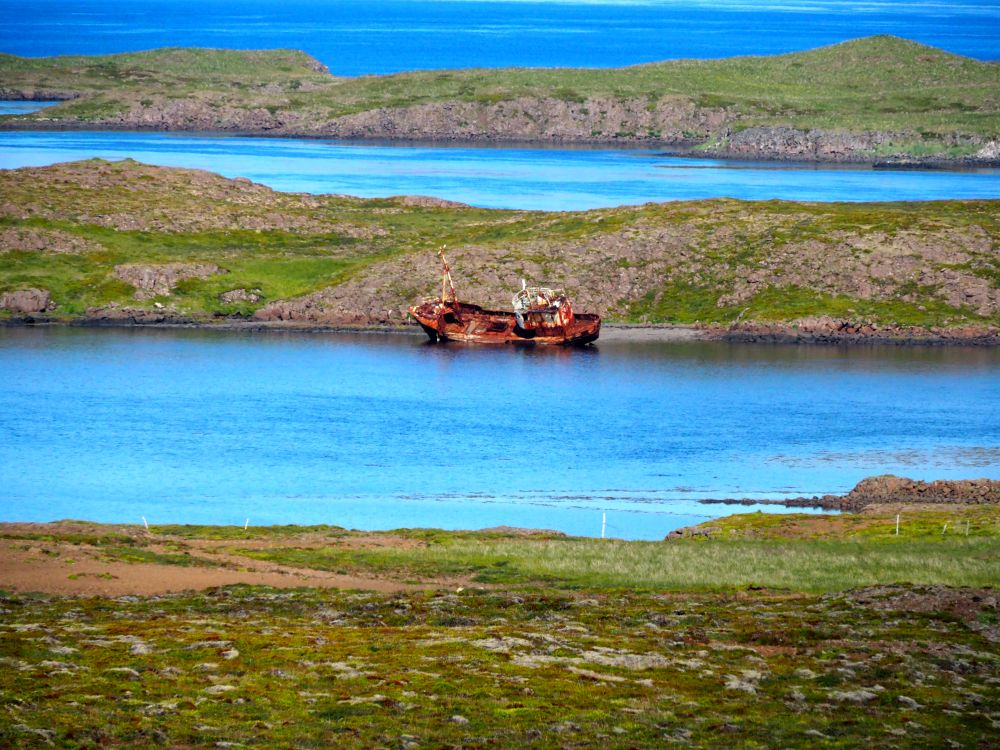 Across a body of water are some islands. Between the shore and the first island is the wreck of a fishing boat. It leans to the side, covered in rust. The water is bright blue here.