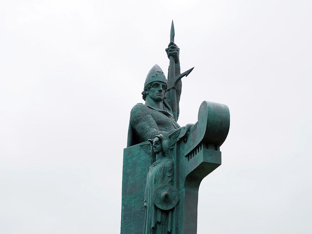 The man is an idealized Viking image: He holds a spear in his left hand pointing straight up. He has a pointed helmet. In front of him is a dragon figure, presumably to suggest a Viking ship. The statue is greenish.