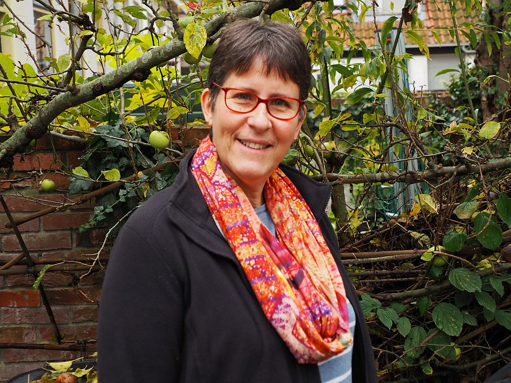 A photo of me from the waiste up. Wearing a black sweatshirt with a scarf around my neck that is patterned in shades of orange and pin. My skin is white, my glasses are red-framed, and I have short brown hair. Behind me is an apple tree.