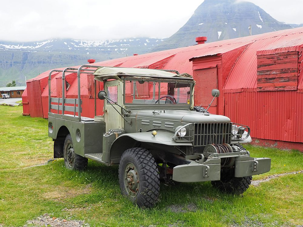 Front and center: a jeep or possibly a rover; it's hard to tell. It is khaki green and has an open back with seats along each side. Behind: a long red building of corrugated metal with a rounded roof: a quonset hut.