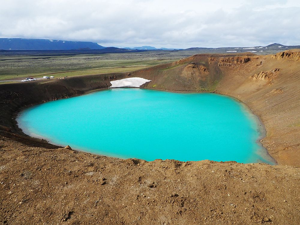 In this photo the crater doesn't look particularly deep, but the water inside it is a brilliant opaque aqua color, surrounded by brown dirt sides.