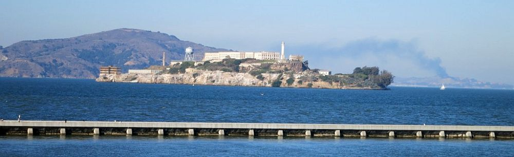 Across blue water, the island of Alcatraz looks like it's topped by a castle. Beyond that, further across the water, a small mountain, and a plume of smoke even further in the distance.
