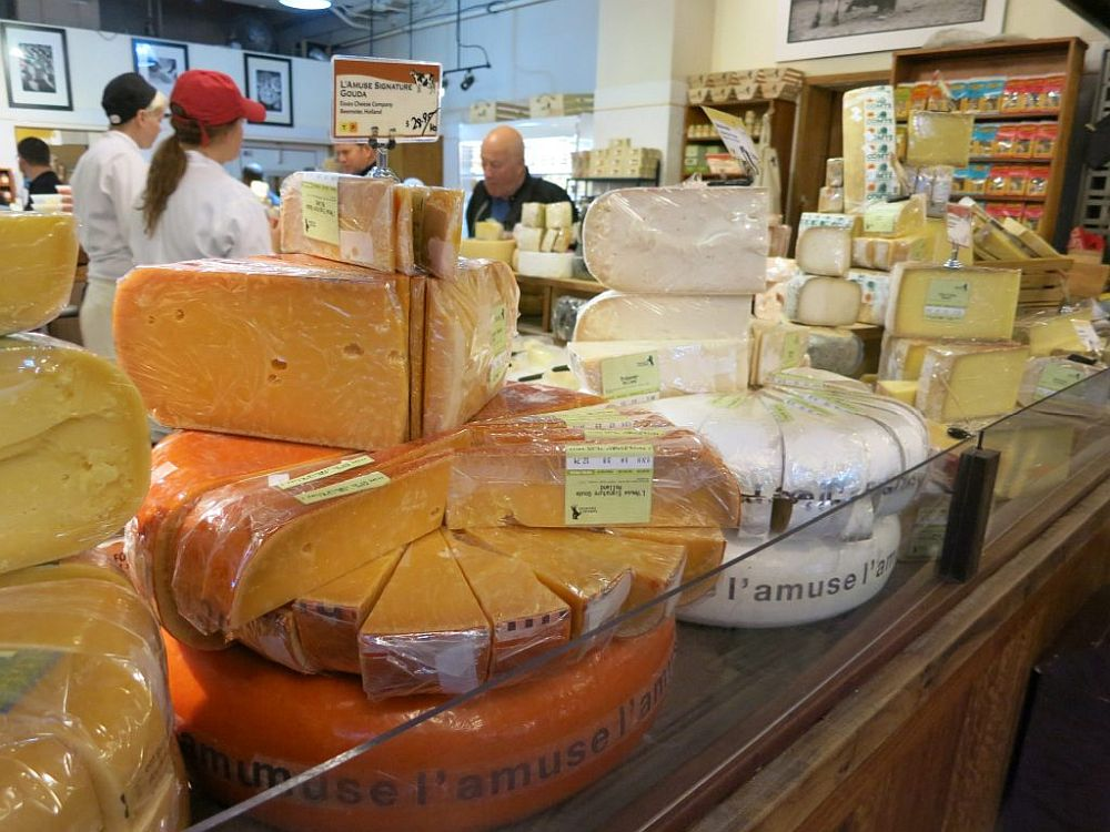 Various cheeses on display in the foreground. Behind, two people in white shirts speak to a customer.