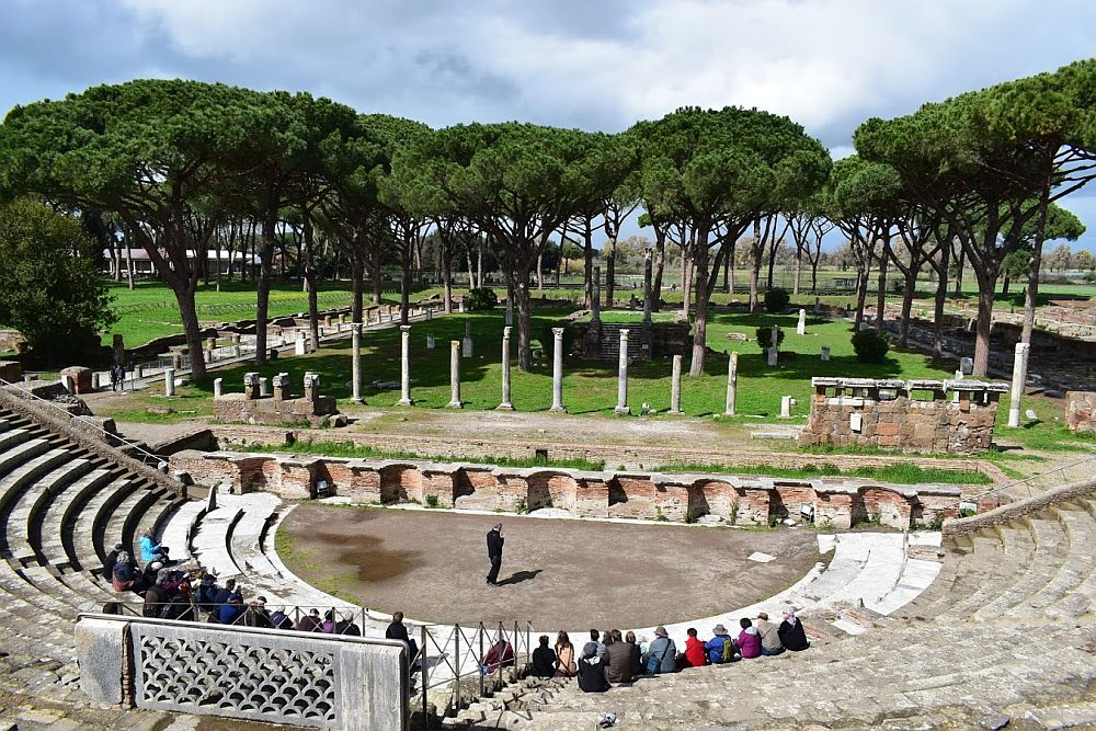 The ampitheater as seen from the top seats. The arc of the stone benches is visible at the bottom of the picture. A semi-circular stage area is at the bottom, and a man stands there, speaking to a small group of people seated on the lowest seats. Behind the stange area is a low wall, and behind that is a row of columns. Behind them is a large area with a number of trees.