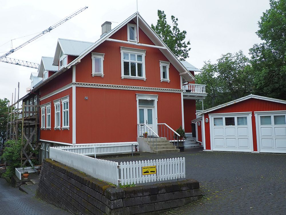 The how is two storeys with an additional small window under the peak of the roof. It is painted bright red with white trim.