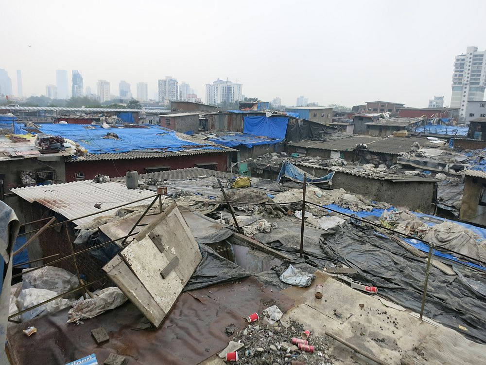 The rooftops look very poor: corrugated iron, but with tarps stretched over portions of them, with stones or other items to hold the tarps in place. In the distance, tall apartment buildings.