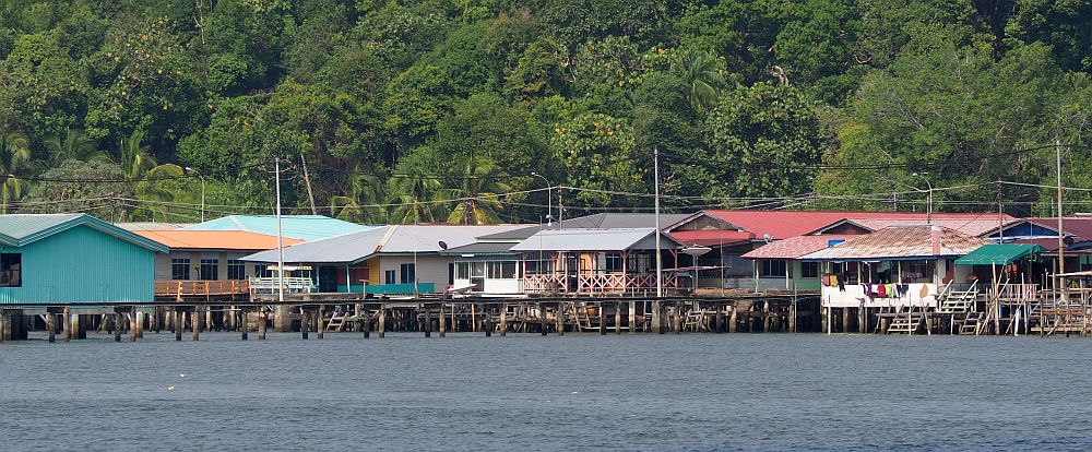 A cluster of houses on stilts over the water, some painted in bright colors, all of them just a single story with wide verandas. One has a lot of laundry hanging from the veranda. Behind is a tree-covered hill.